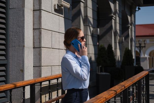 Ritratto di giovane donna d'affari fiduciosa felice che parla al telefono mentre si trova in città all'aperto. vita dei millennial. luce e ombra. foto di alta qualità