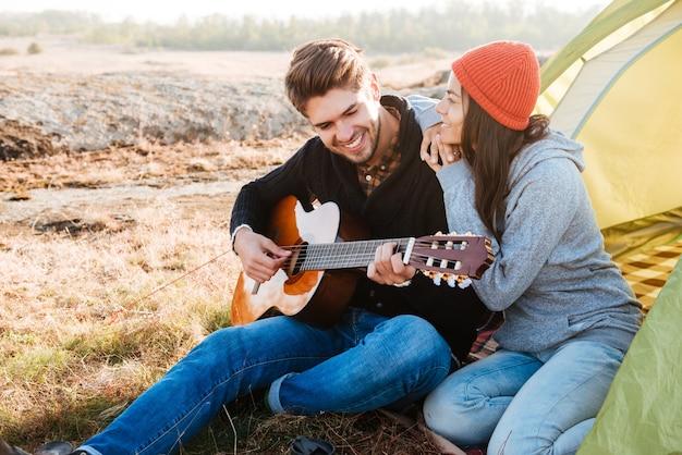 Ritratto di un felice couople con la chitarra che ha campeggio con la tenda all'aperto