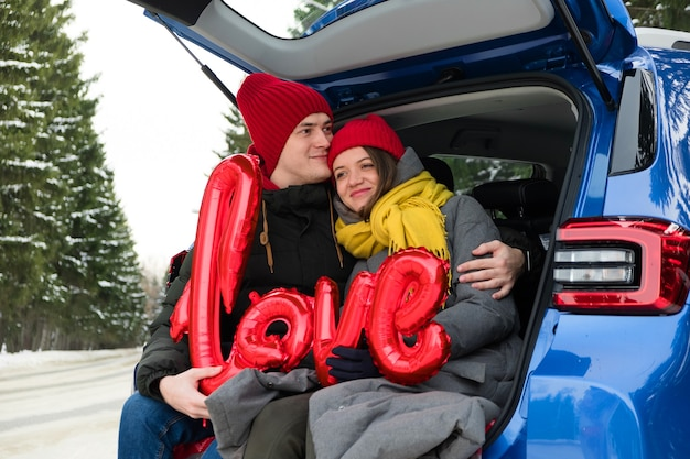 Ritratto felice coppia facce. palloncini a forma di cuore rosso e parola amore. celebrazione di san valentino