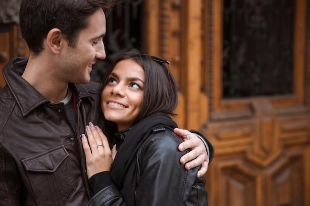 Ritratto di una coppia felice abbracciando all'aperto con la vecchia porta di legno sulla parete