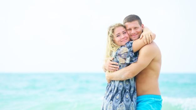 Ritratto di una coppia felice innamorata che si abbraccia sulla spiaggia in estate