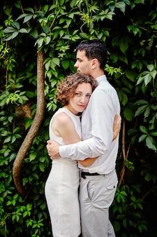 Ritratto delle coppie felici nell'amore che abbraccia nel parco estivo