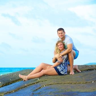 Ritratto di una coppia felice innamorata seduta sulla spiaggia al giorno d'estate