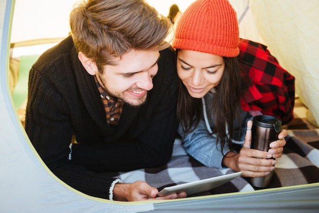 Ritratto di una coppia felice sdraiata in tenda e utilizzando il computer tablet insieme