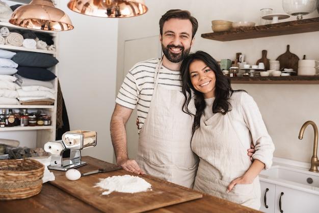 Ritratto di coppia felice uomo e donna 30s che indossano grembiuli che cucinano pasticceria con farina e uova in cucina a casa