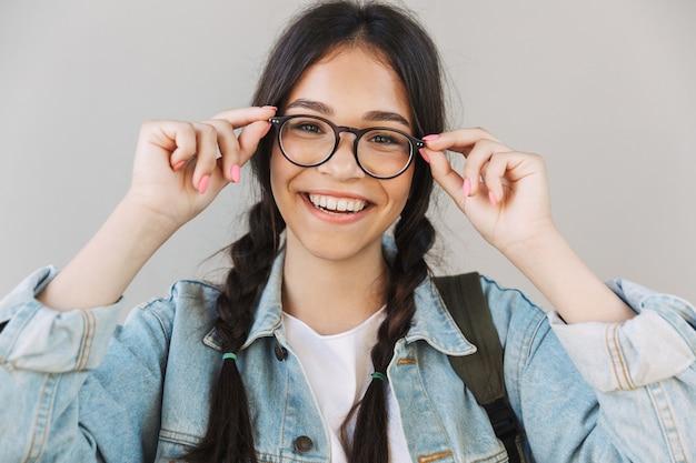 Ritratto di una bella ragazza carina felice in giacca di jeans con gli occhiali isolati sul muro grigio.