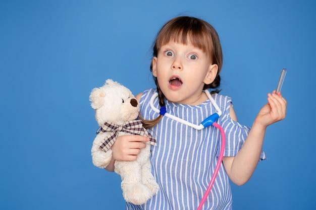 Ritratto di una ragazza carina felice 5-6 anni con uno stetoscopio con nelle mani. il bambino gioca al dottore.