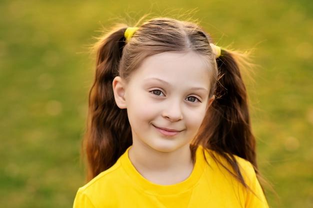 Ritratto di una ragazza carina felice 7-8 anni in natura nel parco estivo.