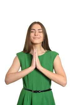 Ritratto di una ragazza carina felice in abito verde che prega