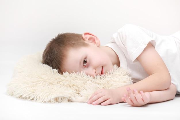 Ritratto di un ragazzino sveglio felice svegliarsi la mattina e sdraiato su un cuscino bianco isolato su uno sfondo bianco. lenzuola fresche e accoglienti. ora di andare a letto per i bambini. concetto di sogni felici.