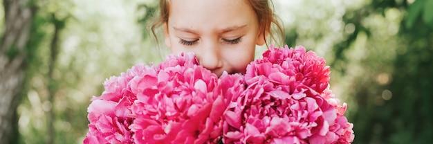 Ritratto di una ragazzina caucasica carina e felice che tiene per mano e odora e si diverte