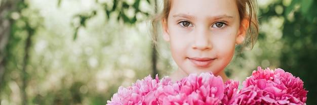 Ritratto di una bambina di sette anni caucasica carina e felice, tiene in mano un mazzo di peonia