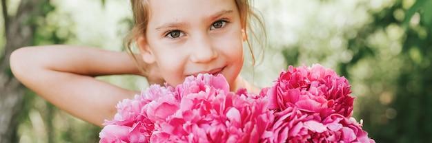 Ritratto di una bambina di sette anni caucasica carina felice, tiene in mano un mazzo di fiori di peonia rosa in piena fioritura e si raddrizza i capelli sullo sfondo della natura. striscione
