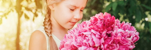 Ritratto di una bambina di sette anni caucasica carina e felice che tiene per mano e odora