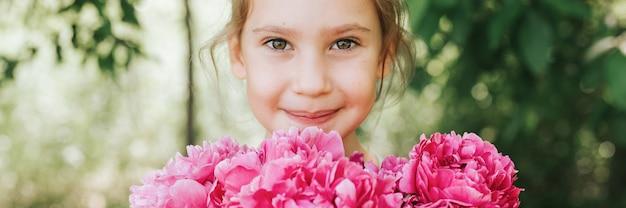 Il ritratto di una bambina felice e carina tiene in mano un mazzo di fiori di peonia rosa