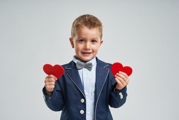 Ritratto di un bambino sveglio felice che tiene cuore rosso e che guarda l'obbiettivo isolato su sfondo grigio