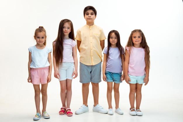 Il ritratto di felice carino ragazzini ragazzo e ragazze in eleganti abiti casual che guarda l'obbiettivo contro il muro bianco