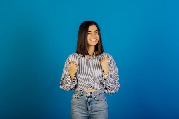 Il ritratto della donna sveglia felice con il sorriso a trentadue denti ha sollevato le mani e celebra la vittoria, il successo isolato sulla superficie blu.