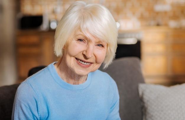Ritratto di una donna anziana felice felice che sorride e che ti guarda pur essendo di ottimo umore