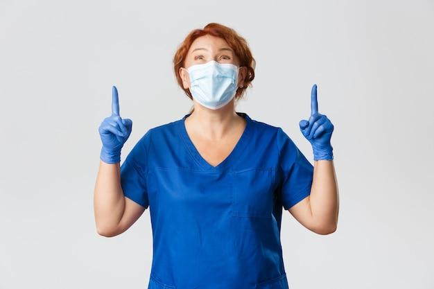 Ritratto di medico felice ammirare qualcosa verso l'alto, infermiera femminile in maschera e guanti guardando e rivolto verso l'alto con espressione gioiosa.