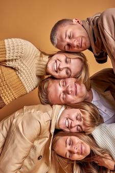 Ritratto di giovani sognanti felici isolati in studio con sfondo marrone pastello