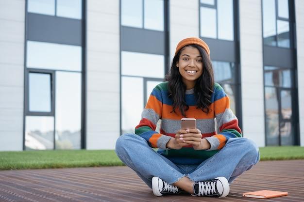 Ritratto di felice studente emotivo studiando, tenendo lo smartphone, concetto di formazione online