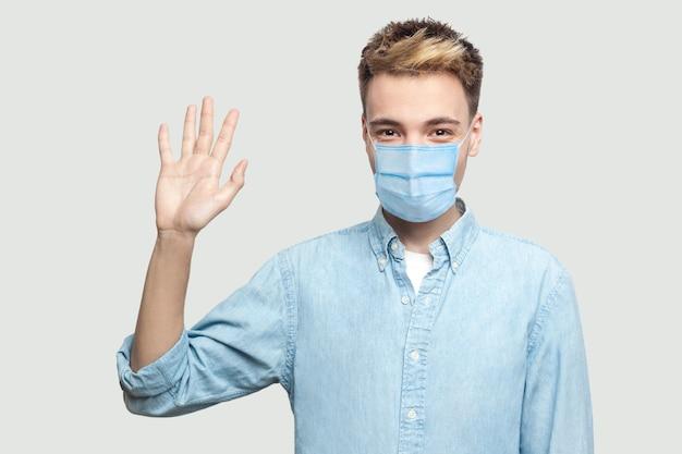 Ritratto di felice eccitato bel giovane con maschera medica chirurgica in camicia blu in piedi, guardando la telecamera e agitando la mano per salutare. studio al coperto girato su sfondo grigio copia spazio.