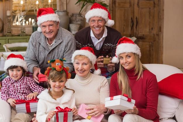Ritratto di una famiglia estesa felice in regali della holding del cappello della santa