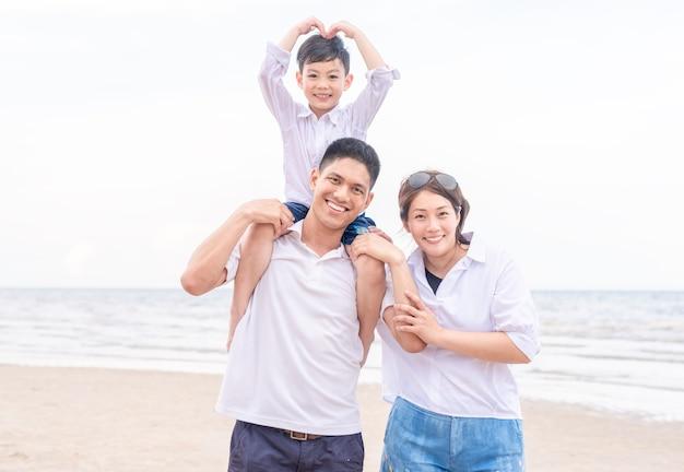 Ritratto felice famiglia e figlio facendo cuore o amore gesto in mare spiaggia
