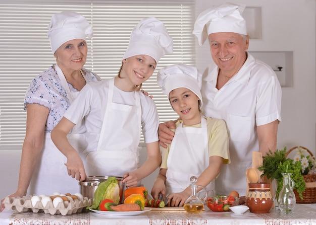 Ritratto di una famiglia felice che cucina insieme ai nipoti