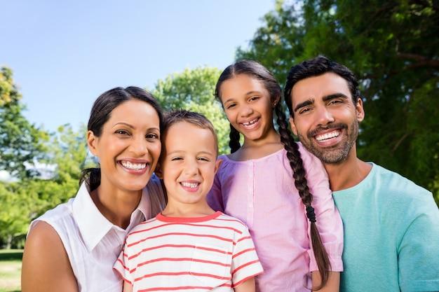 Ritratto della famiglia felice che gode insieme del tempo nel parco