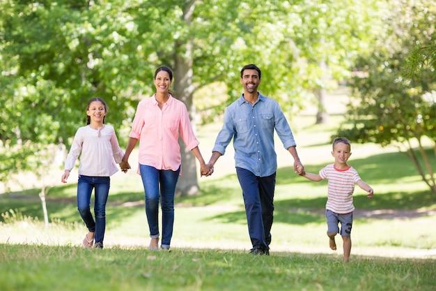 Ritratto della famiglia felice che gode insieme nel parco