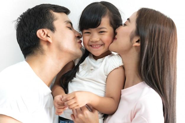 Ritratto del padre e della madre felici della famiglia con la figlia su bianco isolata