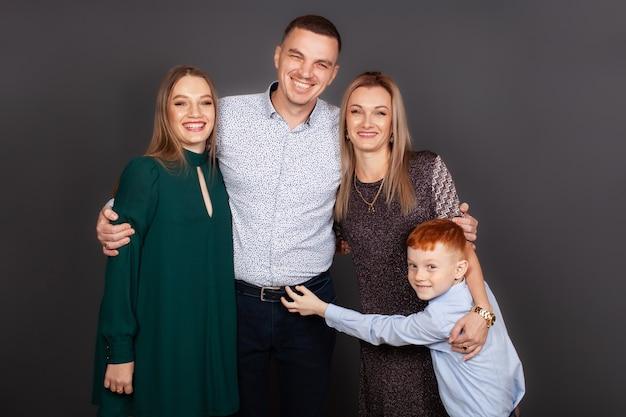 Ritratto di una famiglia felice su uno sfondo grigio in uno studio fotografico