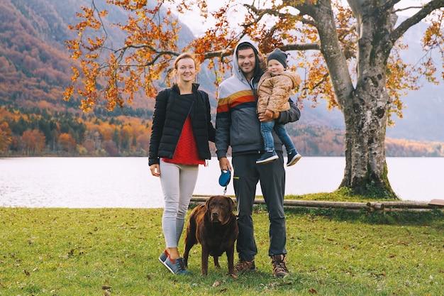 Ritratto di famiglia felice madre padre figlio e cane all'aperto autunno sul lago di bohinj europa
