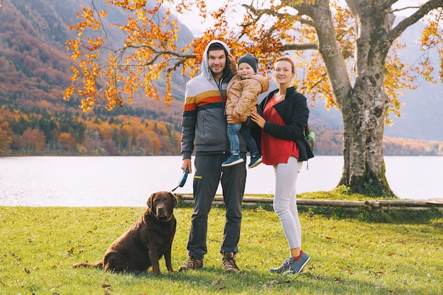 Ritratto di famiglia felice madre padre bambino e cane all'aperto autunno sul lago di bohinj slovenia