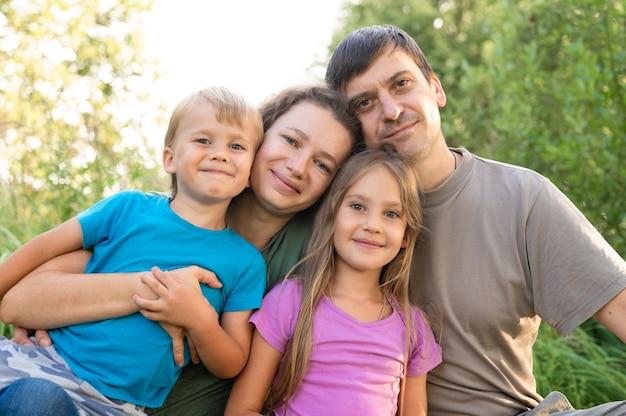 Ritratto di una famiglia felice, madre e padre, figlio e figlia, in natura all'aperto in estate
