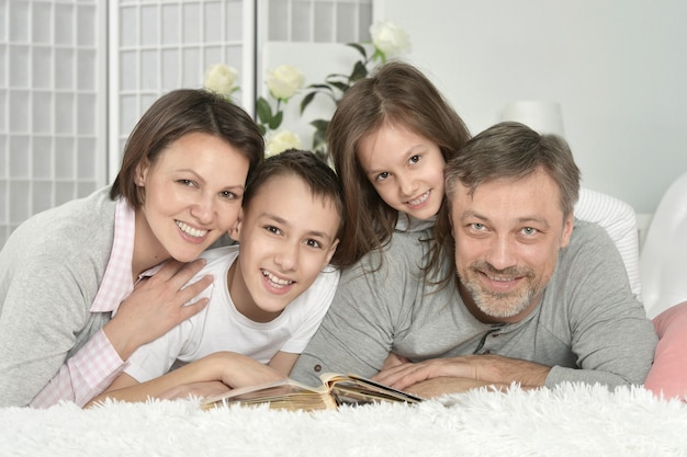 Ritratto di famiglia felice che si rilassa a casa con il libro