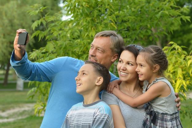 Ritratto di una famiglia felice che si fa selfie nel parco