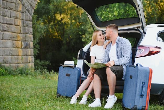 Ritratto di famiglia felice. vacanze, viaggi - famiglia pronta per il viaggio per le vacanze estive. valigie e percorso auto.