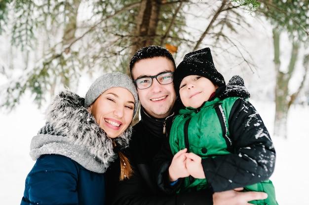 Ritratto della famiglia felice che cammina in un parco di inverno della neve