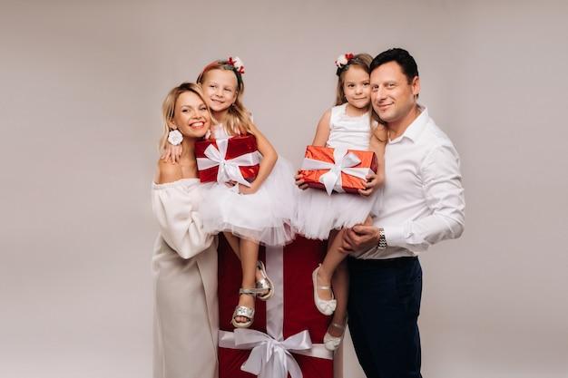 Ritratto di una famiglia felice con doni nelle loro mani su uno sfondo beige.