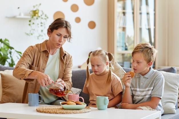 Ritratto di famiglia felice con bambino con esigenze speciali gustando tè e dessert a casa seduti insieme sul divano in soggiorno, copia dello spazio