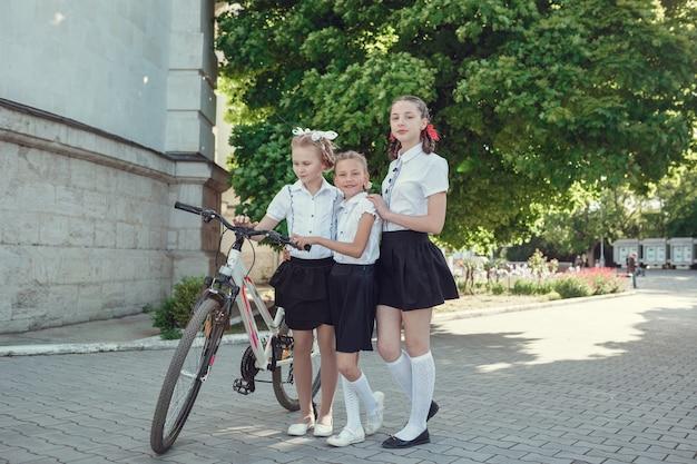 Ritratto di moda felice ragazzini divertendosi con la bici in città.