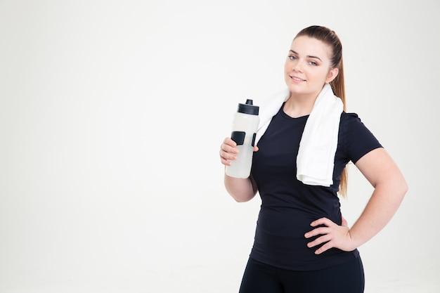 Ritratto di una donna grassa felice in abiti sportivi che tiene in mano uno shaker isolato su un muro bianco