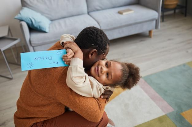 Ritratto di padre felice che abbraccia la bambina dopo essere tornato a casa dal lavoro il giorno del papà, copia spazio