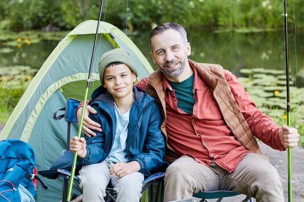 Ritratto di padre felice che abbraccia il figlio mentre vi godete la battuta di pesca insieme e sorridendo alla telecamera