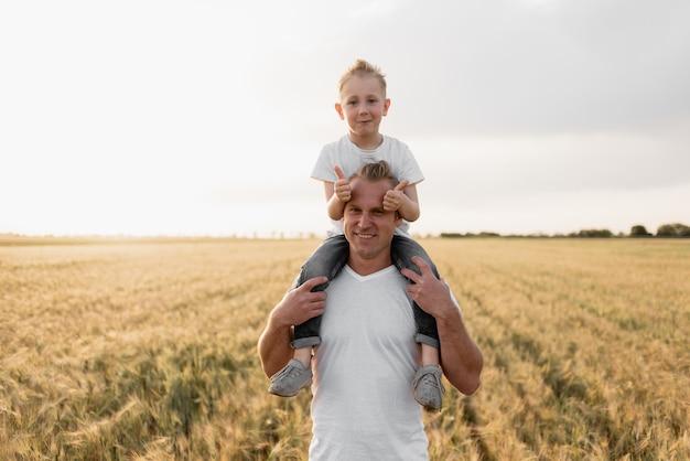 Il ritratto di un padre felice dà a suo figlio un contrailer da cavalcare sulle sue spalle e guardare in alto