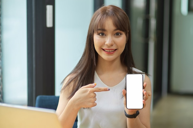 Ritratto di donna felice tenere smart phone con schermo vuoto con interni di ufficio in background