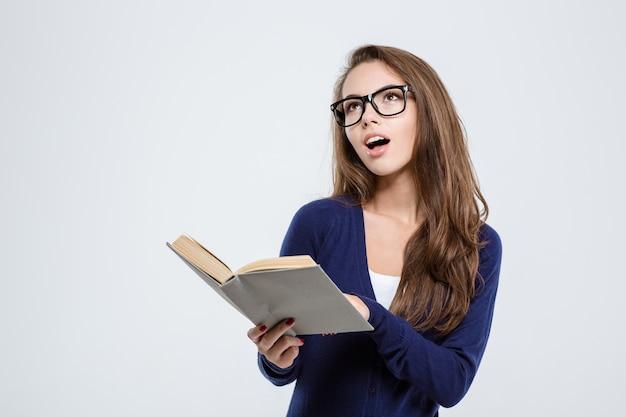 Ritratto di una studentessa felice che tiene in mano un libro e guarda il copyspace isolato su uno sfondo bianco